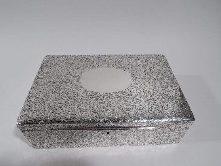 American Art Nouveau sterling silver jewelry box, circa 1910. Rectangular with straight sides. Cover hinged and gently curved with long tab. Dense scrolling flowers engraved allover. Cover top has large oval frame (vacant). Box and cover velvet