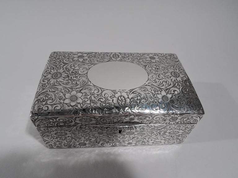 American Art Nouveau sterling silver jewelry box, circa 1910. Rectangular with straight sides. Cover hinged and gently curved with tapering tab. Dense scrolling flowers engraved all-over. Cover top has large oval frame (vacant). Box and cover velvet