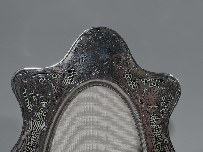 American Art Nouveau sterling silver picture frame, circa 1900. Narrow oval window in wavy-shaped surround with bracket feet. Open ornament with leaves, flowers, and shells on irregularly speckled green and white ground. Top solid with scrolled