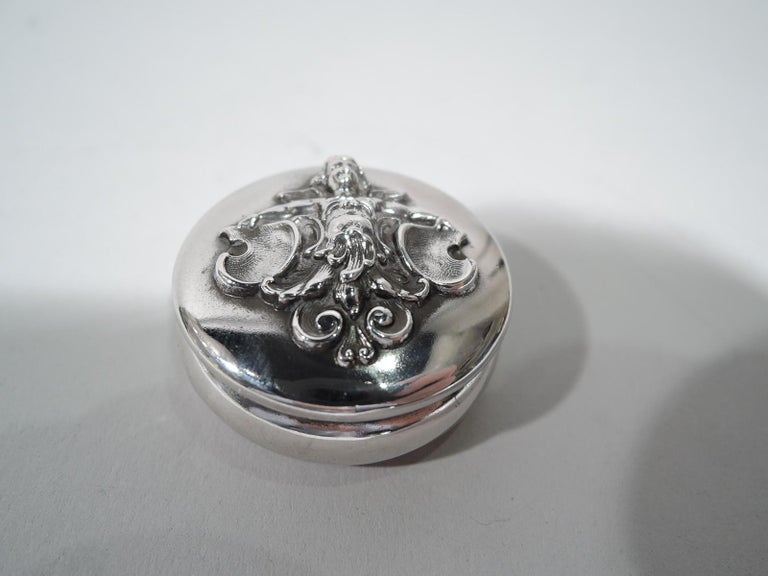 Turn-of-the-century Art Nouveau sterling silver pillbox. Made by William B. Kerr in Newark. Round and bellied with hinged cover and fixed ring mounted to top. On cover is applied a winged cherub—a fantasy figure to lull you into fairyland. Fully