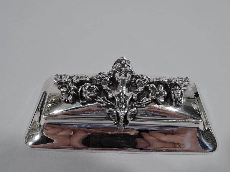 Art Nouveau sterling silver postage stamp box. Made by William B. Kerr in Newark, circa 1900. Rectangular on spread base. Cover hinged and raised with applied floral garland, a female head at center. A splendid and tactile take on the