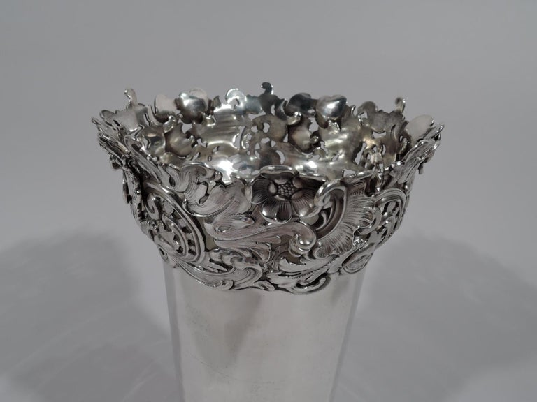 Art Nouveau sterling silver vase. Made by Redlich in New York, circa 1900. Plain cylinder with substantial leafy-scroll and flower mounts applied to base and rim. An unusual contrasting design. Fully marked and numbered 1682. Weight: 17 troy ounces.