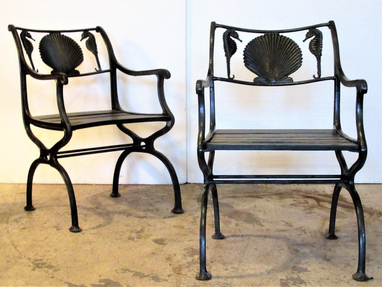 Pair of antique American black painted cast iron garden chairs with curved arms, wood plank seats and finely detailed sea horse and scallop shell design at top rails. They are stamped in iron at upper side seat rail Marcy Foundry - NY, NY patent