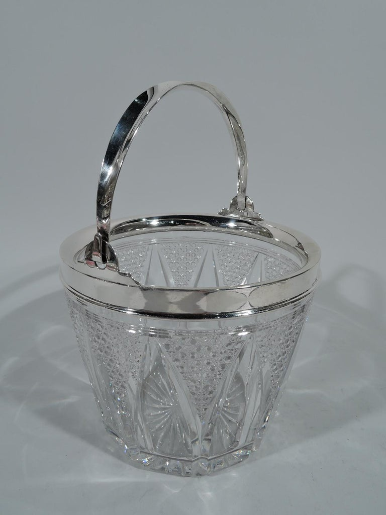 Turn-of-the-century cut glass and sterling silver ice bucket. Made by Wilcox Silver Plate Co. (a division of International) in Meriden, Conn. Round clear glass with band of stylized leaves, and diaper triangles with facets and starts. Sterling