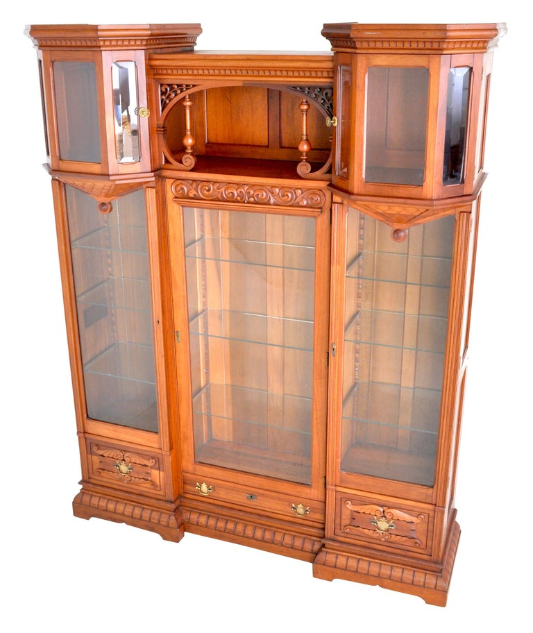 Antique American Eastlake walnut breakfront bookcase/hutch/cabinet, circa 1890. To the center is an area with pierced brackets and turned supports flanked by two turret style doors with beveled glass, the turrets having dentil molding to the top and