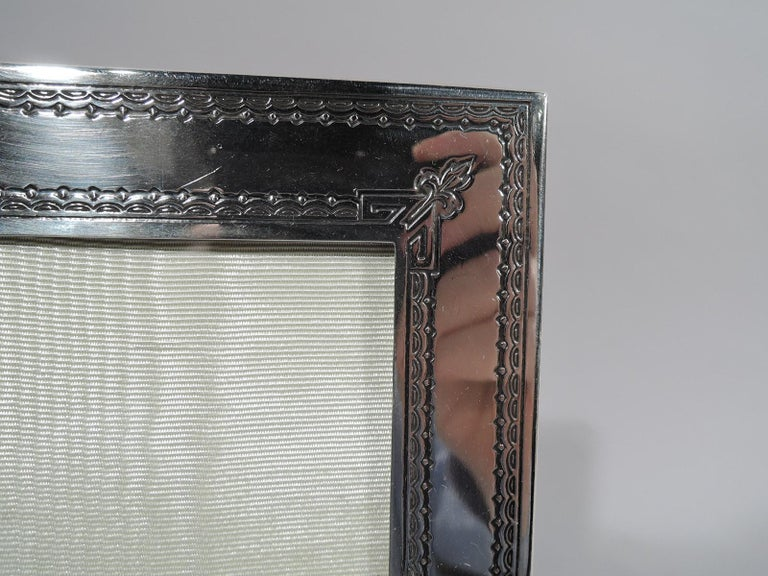 Edwardian classical engraved and acid-etched sterling silver picture frame. Rectangular window in flat surround with rosette rondels on sides and leaf in trapezoid on bottom rail. Top rail has inverted trapezoid (vacant). Ornamental borders and