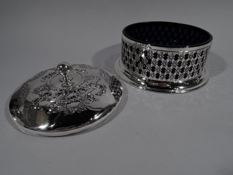 Turn-of-the-century American Edwardian sterling silver box. Retailed by Black, Starr & Frost in New York. Round with plain and solid spread foot. Sides open basket-weave with beaded flower heads. Cover gently raised with ball finial chased ornament