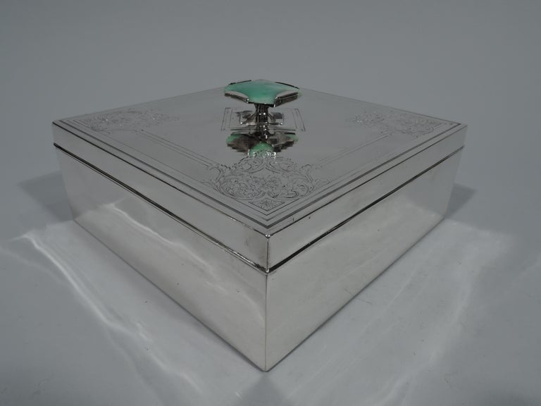 Edwardian sterling silver keepsake box. Square with straight sides and sharp corners. Cover flat with engine-turned ornament, diagonal lines bordered by dense waving. Corners have engraved scrolls and flowers. Mottled green agate finial. Fully