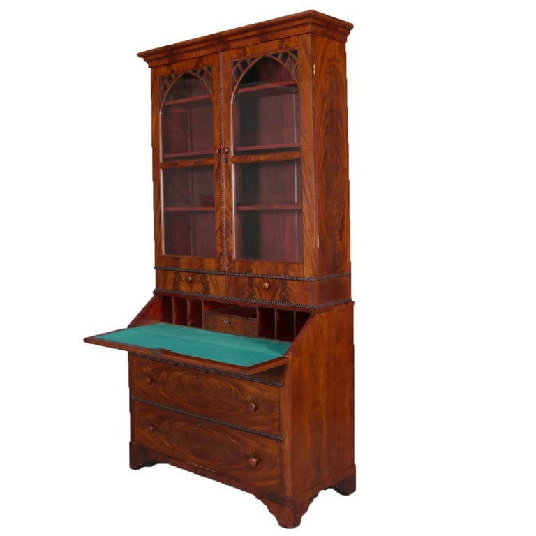 Antique American Empire flame mahogany secretary features upper bookcase with double fretwork and arch form glass doors opening to shelved interior and over secretary with drop front desk having felt writing surface and pigeon holes over case with