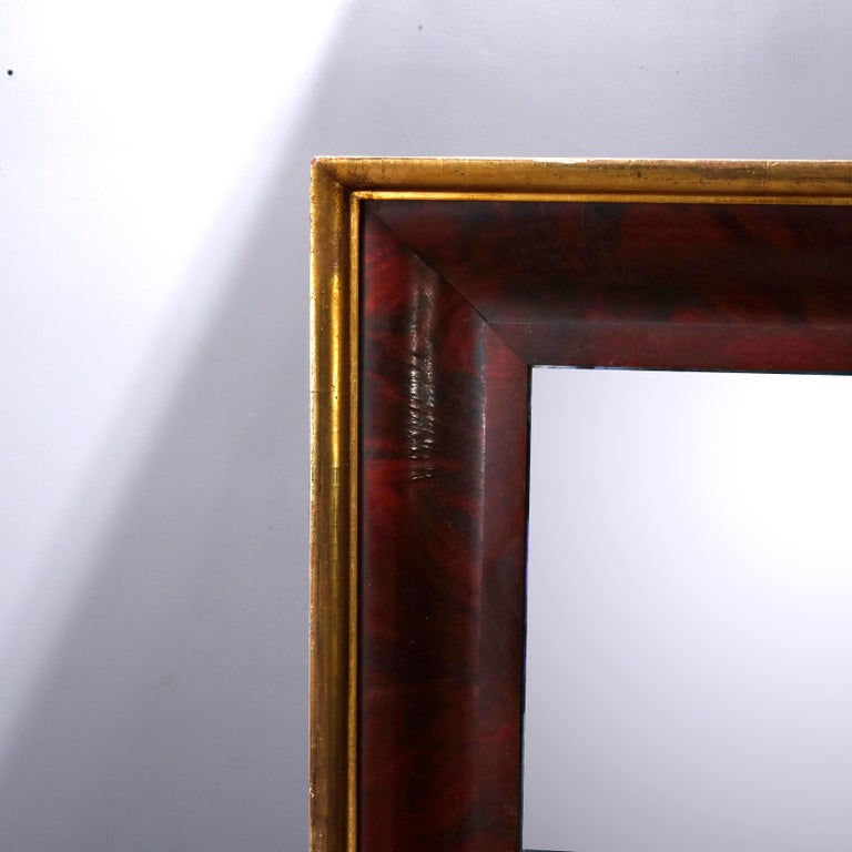 An antique American Empire trumeau wall mirror offers a flame mahogany ogee frame with gilt bordering and housing double beveled mirrors, 19th century  ***DELIVERY NOTICE – Due to COVID-19 we have employed LIMITED-TO-NO-CONTACT PRACTICES in the