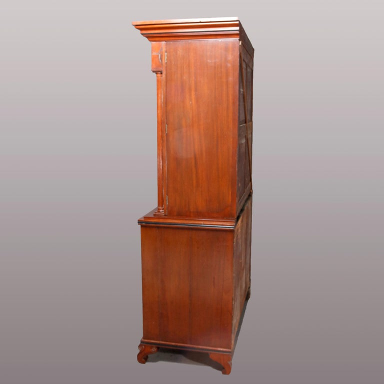 An American Empire Quervelle School linen chest offers flame mahogany construction with upper having arched and crossbanded doors with flanking support columns and opening to reveal three pull-out linen trays, lower chest having two smaller drawers