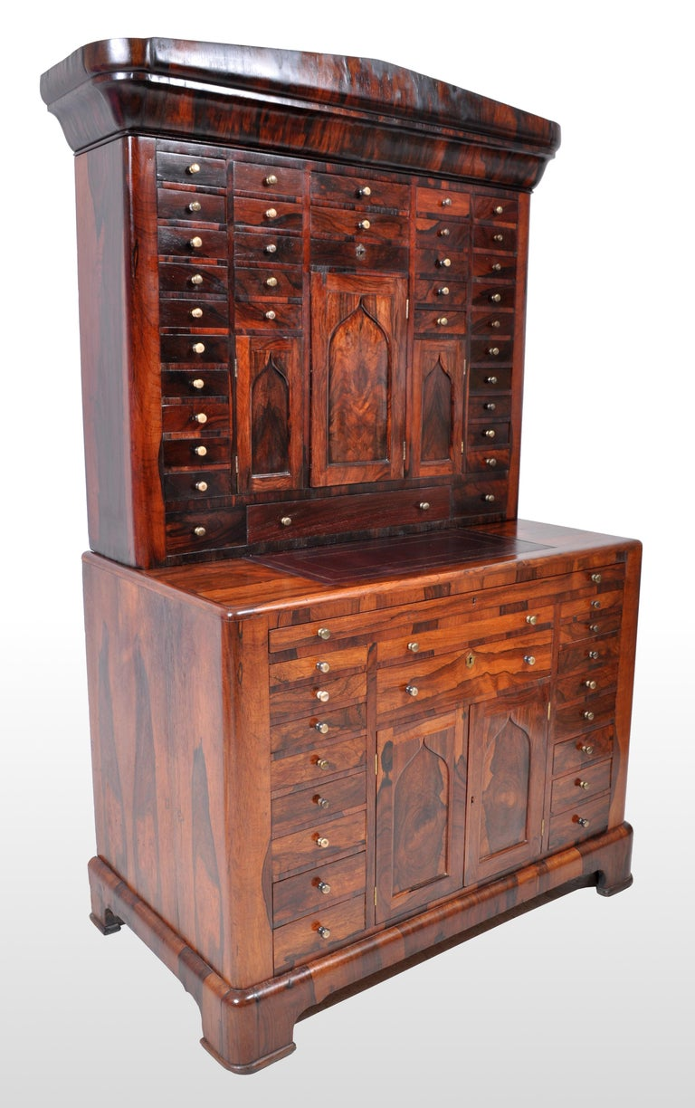 Antique American Empire rosewood dental / medical cabinet, circa 1820. This incredibly rare cabinet, in two section, made of figured rosewood throughout and having a neoclassical pediment to the top. Below the pediment is a cabinet with 34 drawers