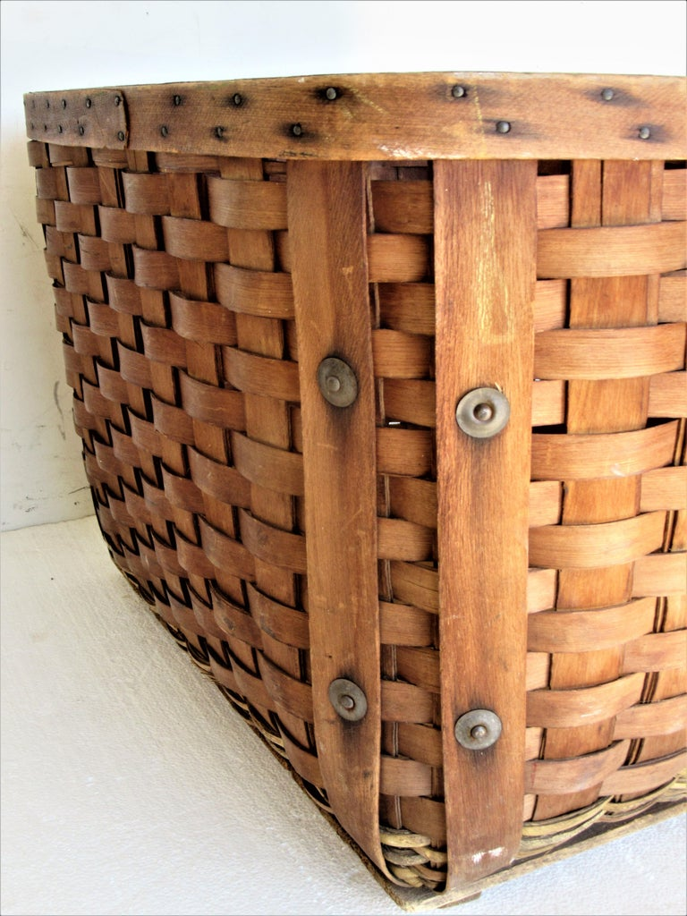 Antique hand crafted bent wood / splint and woven wicker large storage or gathering basket with two handles, tin metal buttons and wood planked bottom. A very good quality structurally solid fully functional decorative basket in overall beautifully