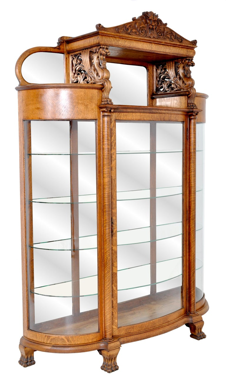 The cabinet made of quarter sawn oak and having a carved lion's mask pediment to the top and flanked with stylized carved foliate, below are a pair of carved winged griffin supports with corresponding pierced foliate carving. To the rear of the