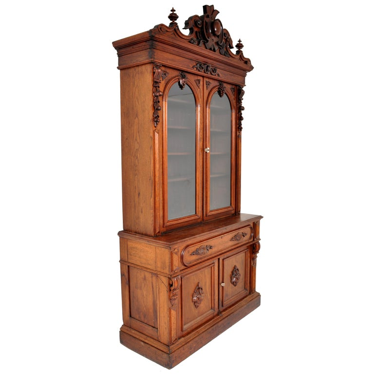 A very grand antique American Renaissance Revival carved bookcase secretary, circa 1870. The bookcase in two parts, the top bookcase having an ornately carved crown with floral and architectural detail and flanked by twin turned finials. Below are