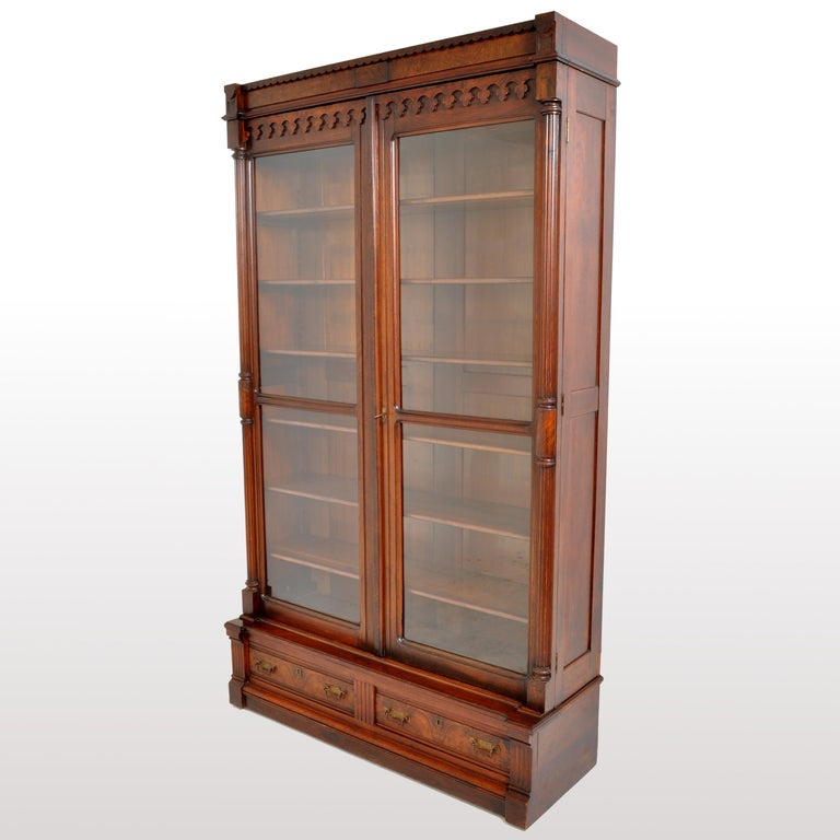 A fine antique American Eastlake/Renaissance Revival, tall, walnut and burl-walnut bookcase, circa 1875. The bookcase having a carved crown with a carved gallery below, the twin doors each having a full length ribbed and turned column. The doors