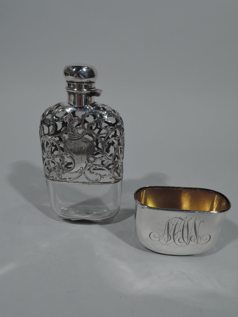 Turn-of-the-century Art Nouveau clear glass flask with silver overlay. Top part overlaid with engraved silver scrollwork and asymmetrical cartouche dated 1899. Bottom part has solid detachable cup with interlaced script monogram. Short neck in