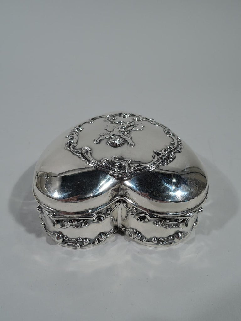 Romantic heart-form sterling silver jewelry box. Straight sides and hinged and raised cover. Applied ornament. Sides have scrolls and cover has gleeful arms-raised-high cupid in scrolled wreath. Box interior velvet lined. Cover interior gilt-washed.