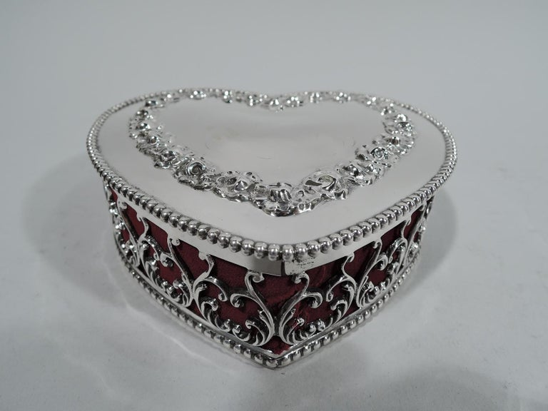 American Victorian sterling silver jewelry box. Heart form. Solid bottom and open sides with leafing scroll pattern. Cover solid and hinged with applied heart. Beaded rims. Box interior has crimson velvet liner. A flaming, gushing gift. Fully marked