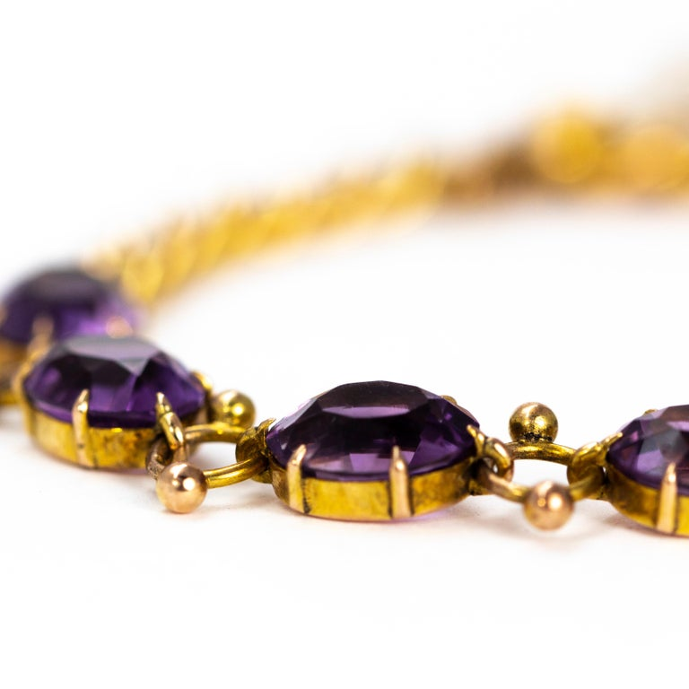 The stones in this bracelet are a gorgeously rich purple colour. They are set in simple claw settings and are connected with orb detailed links. The other half of this bracelet is made up classic curb links.   Length: 7inches Stone Dimensions: 7x