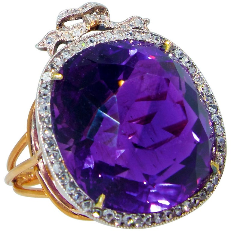 Antique ring in silver and gold possessing a very fine natural Siberian amethyst displaying  a pure royal purple color with a hint of red - the classic Siberian color seen in 19th century jewelry.  This center stone weighs approximately 28.5 cts and