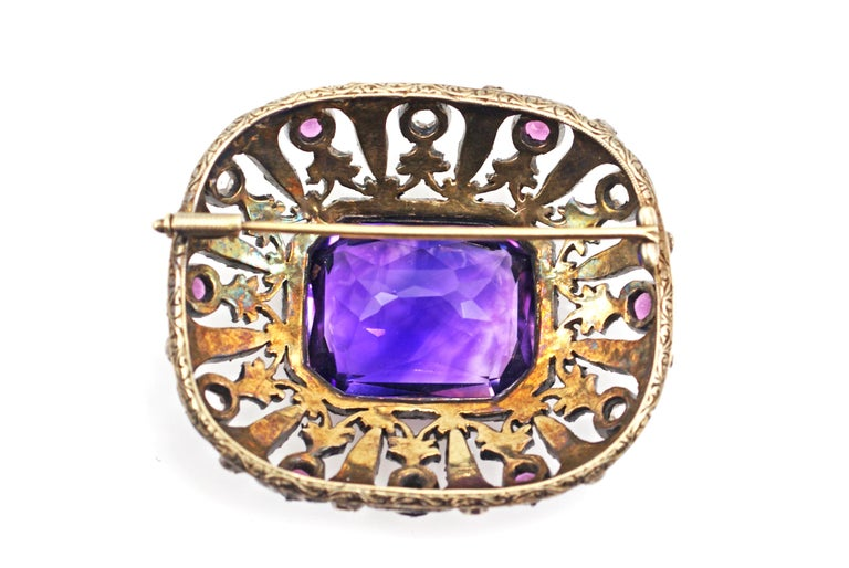 An amazing amethyst measured to weigh approximately 30 carats is the center piece of this incredible antique brooch. The faceted extremely well cut Amethyst displays a unique color saturation of deep bright purple with slight shimmers. The Amethyst