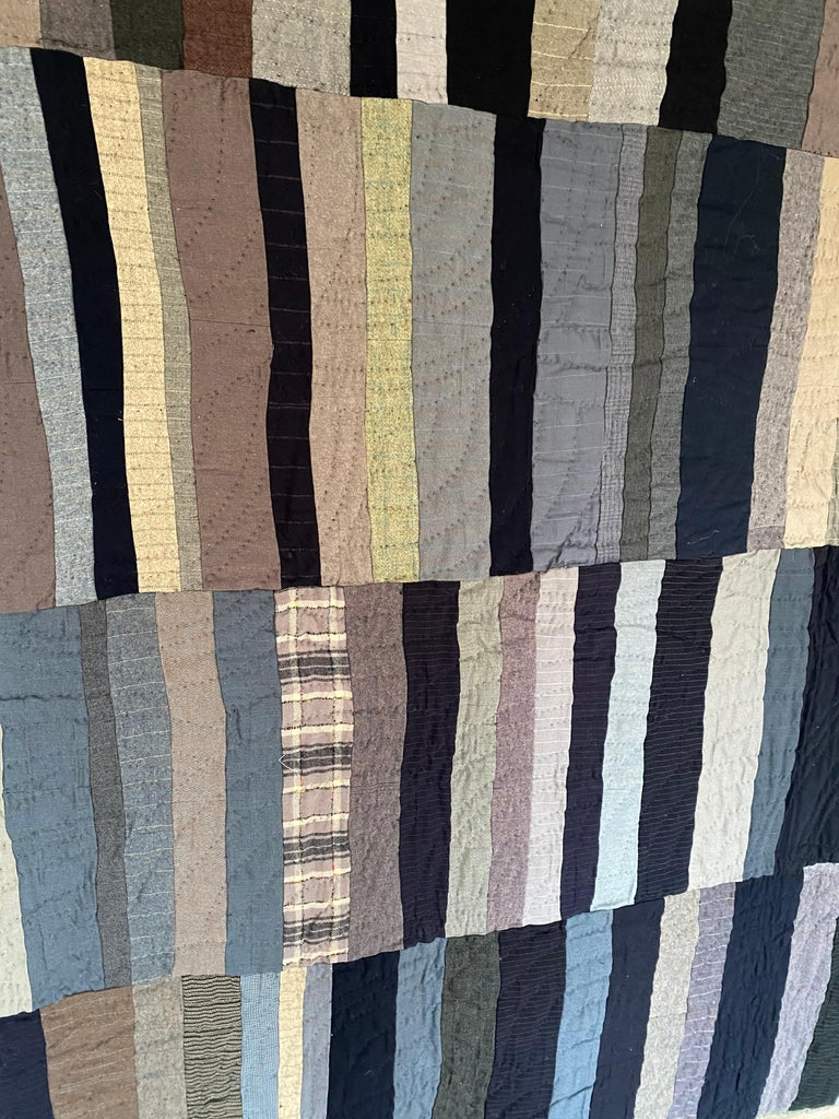 An antique Amish multi stripe patchwork quilt. Consisting mainly of bars produced from suiting fabric. Wonder tonal design.