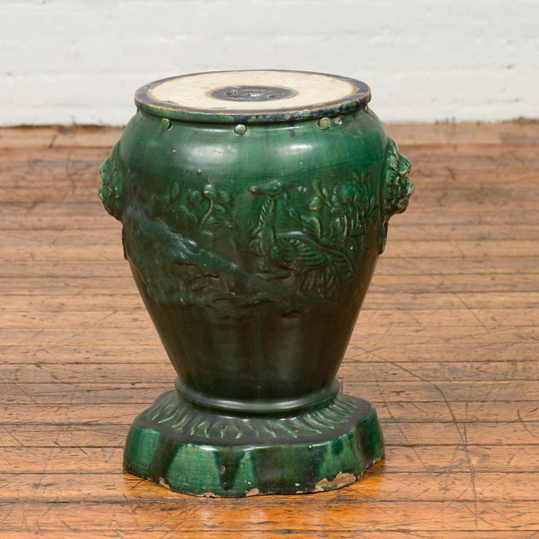 An 18th or 19th century Annamese garden seat from Vietnam with green glaze and shaped base. Made of ceramic and boasting a green glaze, this garden stool, which was also used as a pedestal for a garden planter, features a circular Silhouette,