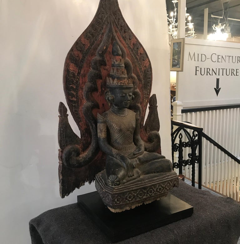Rare large Thai Buddha sculpture from the mid-19th century. The central figure with shield back retaining some original color and paint. Some expected chipping and wear to original sculpture with a recent black painted wood base.