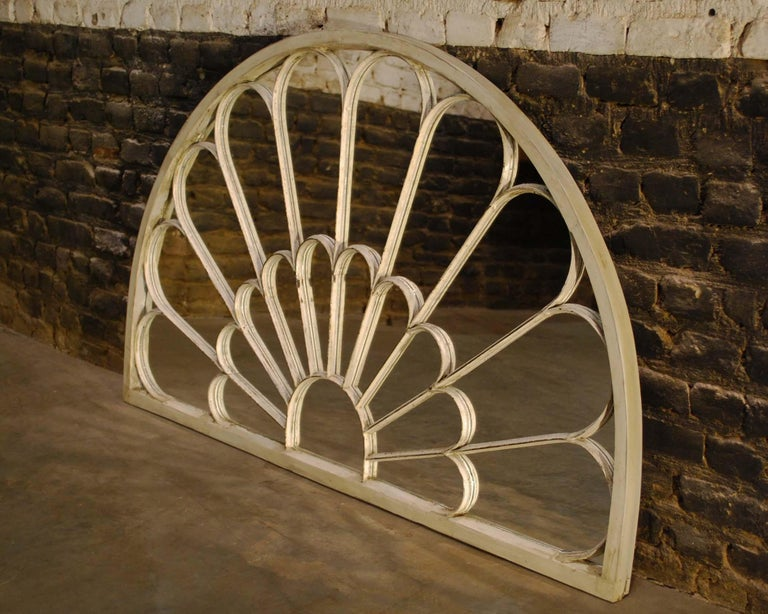 This elegant antique fanlight is made in the UK, circa 1910. It has a solid pine outer frame with cast iron mullions. Originally situated over a double door or large window, this fanlight is converted to a stylish mirror in our atelier. It was