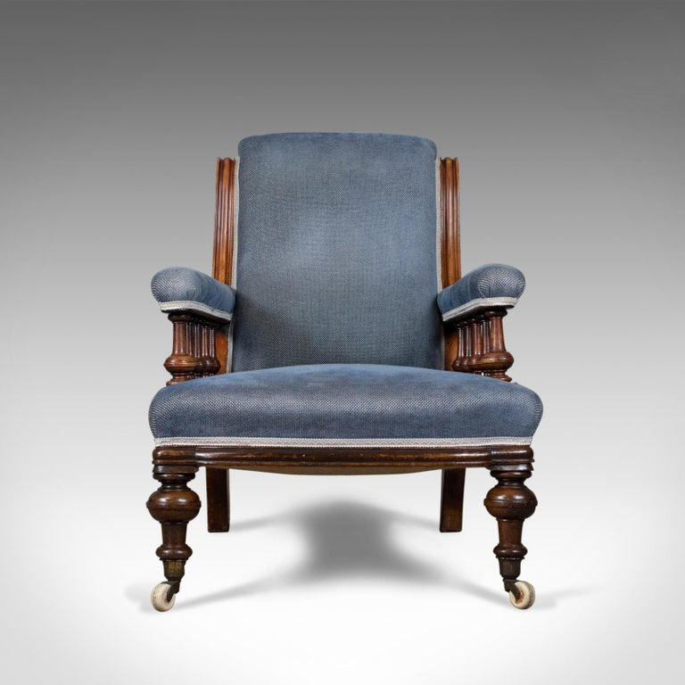 This is an antique armchair, an English, Victorian, club chair, walnut with blue upholstery, dating to the late 19th century, circa 1880.  Walnut framed offering a comfortable, deep seat Raised on turned legs to the front and swept square section