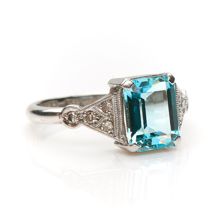 Art Deco, aquamarine and diamond ring, circa 1930. Set to centre a step-cut aquamarine flanked by trumpeting diamond set shoulders all finely finished with millegrain boarders. The aquamarine is a very pretty hue of blue, it creates a beautiful