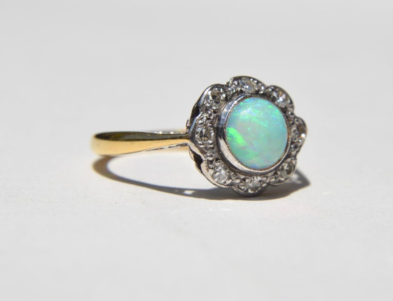 Lovely and sweet antique English origin Art Deco era circa 1920s .84 carat (6mm diameter) fiery blue green Australian opal round cabochon with 8 sparkling round cut diamond halo. 18K yellow gold. Each diamond measures 2mm, .03 carat each. Marked as