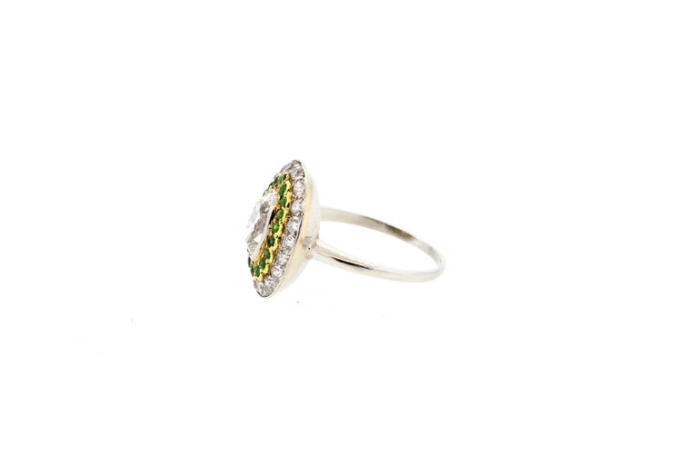 A fine antique Art Deco marquise shape diamond ring accented by demantoid garnets dating to 1920. The ring centers on an old cut marquise diamond that weighs approximately 0.95 carats and is graded as an H color and VS clarity. There are 20 round