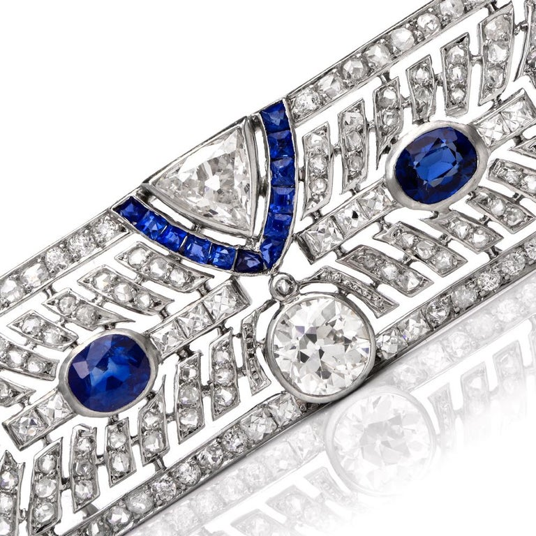 This timeless antique diamond and sapphire pin brooch is crafted in solid platinum. Displaying of geometric art deco patterns set in round-cut, square-cut, and triangular-cut diamonds weighing approx. 3.50 carats, graded H-I color, and VS2-SI