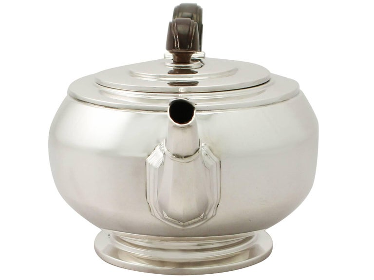 A fine and impressive antique George VI English sterling silver teapot in the Art Deco style, an addition to our silver teaware collection.  This fine antique George VI sterling silver teapot has a plain circular rounded form onto a circular