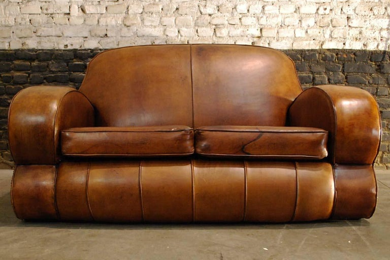 This beautiful two-seat sofa is upholstered in its original hand patinated sheep leather. It was made in France and dates approximately 1915. It's shape and construction make it a typical Art Deco club sofa. The sofa has been upholstered with the