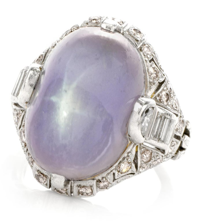 This stunning antique natural art deco lavender genuine star sapphire and diamond ring is crafted in solid platinum, weighing 14 grams and measuring 21mm x 12mm high. Exposing a one prominent prong-set, oval shaped, genuine star sapphire all natural
