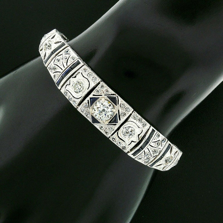 This gorgeous antique filigree bracelet was crafted from solid 900 platinum during the art deco period. It features a beautiful, GIA certified, old European cut diamond prong set at its center. This center diamond is exceptionally brilliant and
