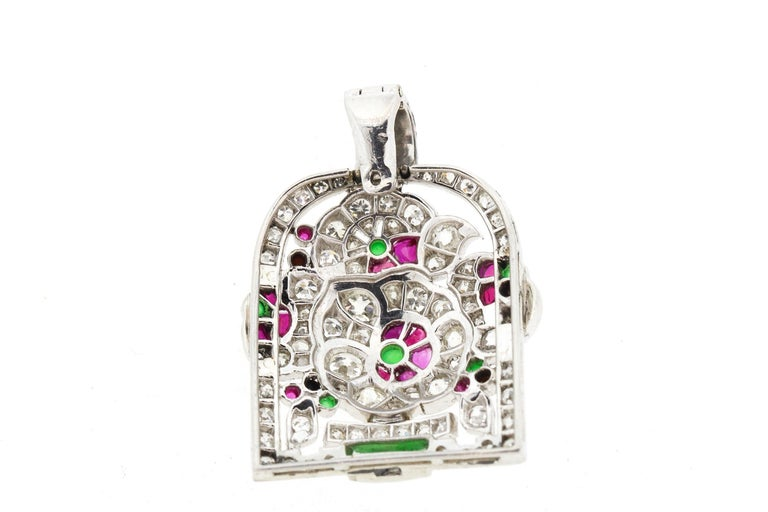 An antique Art Deco diamond and gem set jardiniere pendant made in platinum circa 1920. This pendant is a colorful rendering of a potted flower set with buff top rubies, chrysoprase and onyx. The pendant is dimensional and bright. The bail opens up