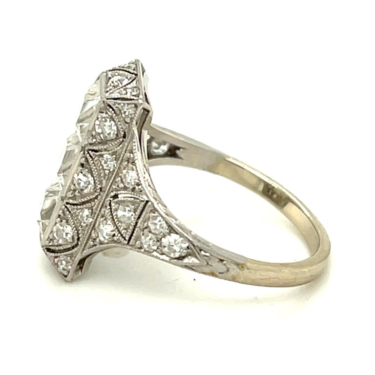 Antique Art Deco filigree platinum diamond ring centering upon three French Cut diamonds, circa 1920. The three white and clean diamonds weigh approximately 0.75 carats each. The mounting has  28 single cut diamonds weighing an additional 0.70