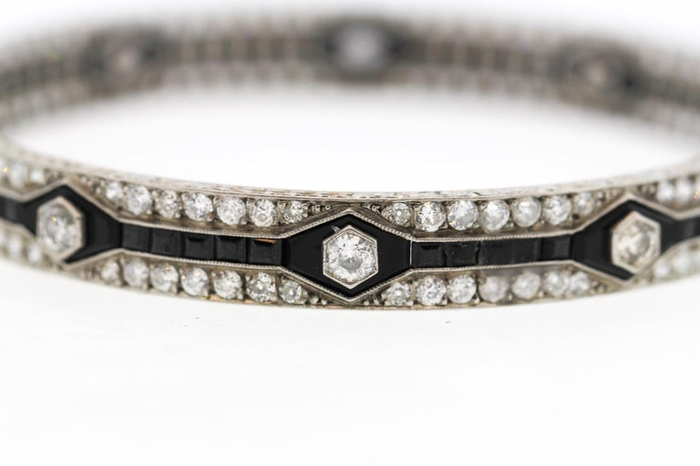 A spectacular Art Deco platinum onyx and diamond bangle bracelet, circa 1920. This bracelet has a strong geometric pattern created by the calibre cut onyx. It is set with Old European Cut diamonds, 150 stones weighing approximately 12.50 carats. The