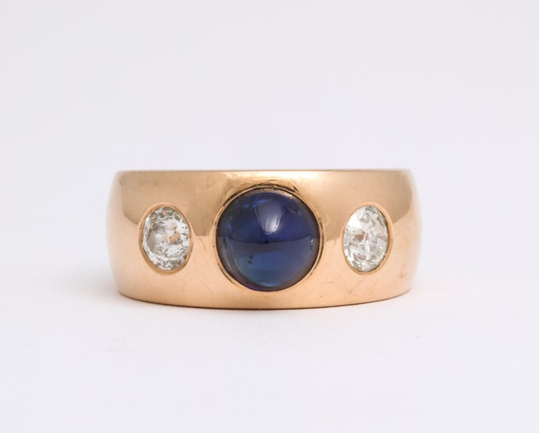 Solidly Art Deco in design, solid in weight, this stunning 18 Kt gold band is set with a sugarloaf natural sapphire, (a cabochon cut gem that rises to a dome), weighing 1.6 Cts and two European cut diamonds totaling approximately 1 Ct in weight. The