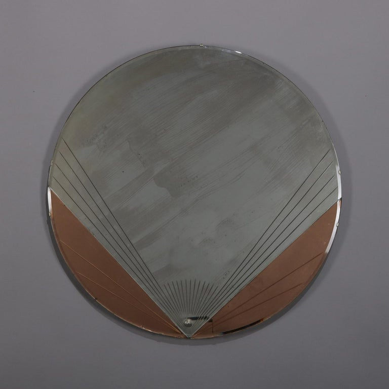 Antique Art Deco wall mirror features circular form with stylized fan in two-toned copper and silver backing, en verso original label, circa 1920