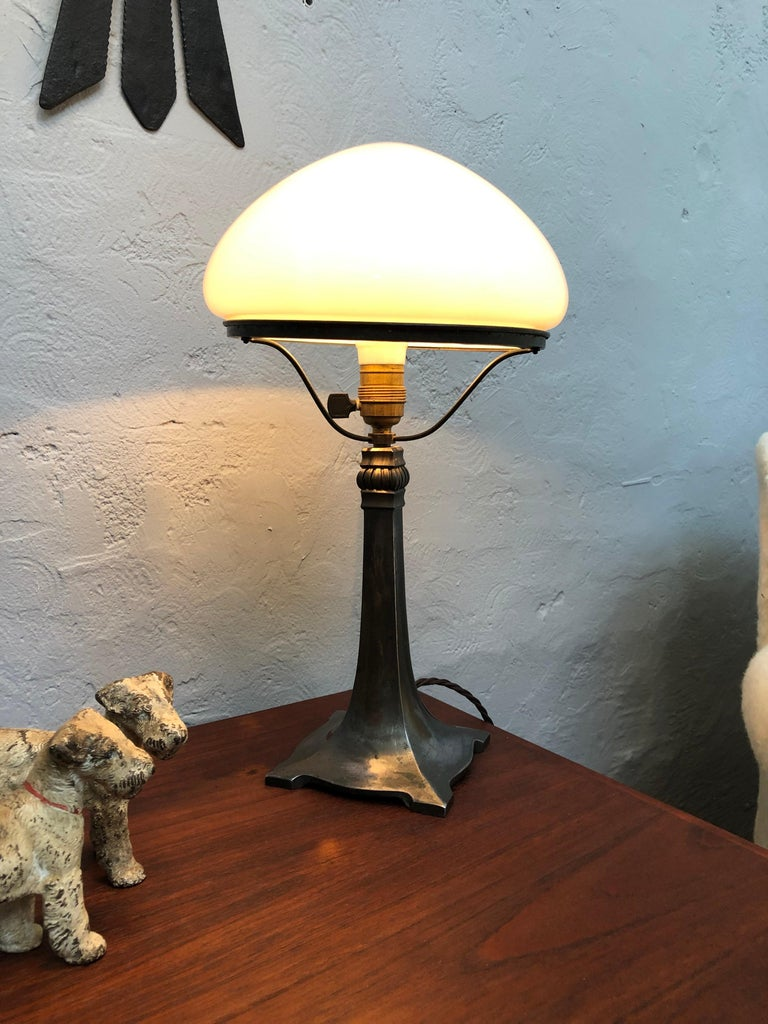 Antique Art Deco table lamp with a beautiful stylish elegant cast alloy base and with a hand blown opaline glass shade.  Still with the original ceramic and brass bulb holder with an off/on switch.  The lamp has been rewired with a brown twisted