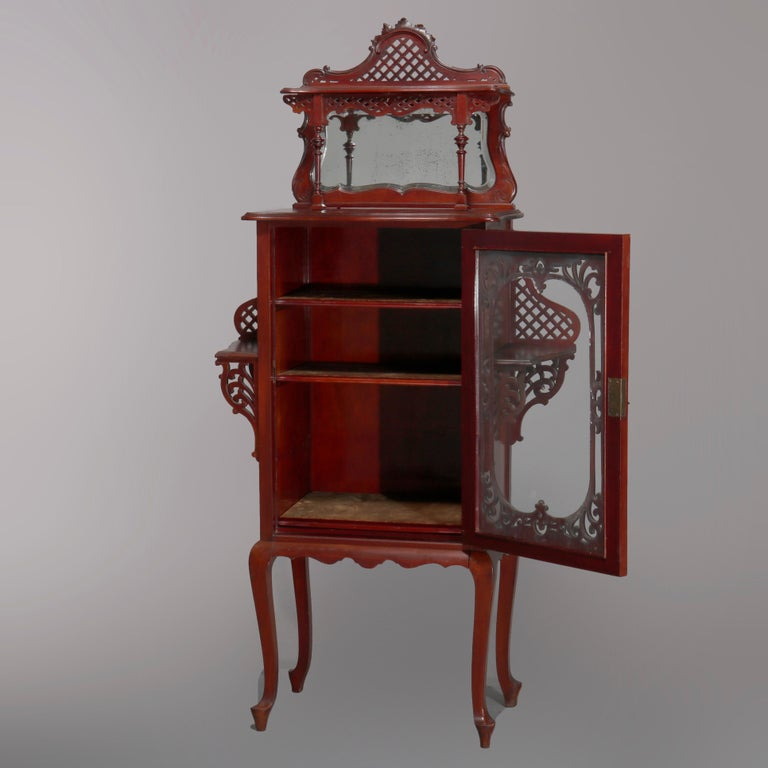 An antique Art Nouveau étagère offers mahogany construction with upper display over beveled mirror backsplash surmounting single door case having flanking display shelves, raised on cabriole legs, carved reticulated lattice, scroll and foliate