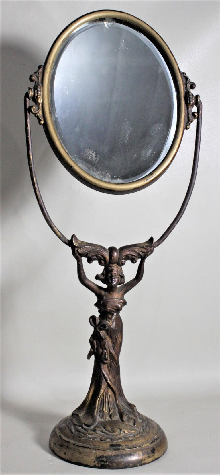 This antique cast figural ladies pedestal dresser mirror is unsigned, but presumed to have been made in France in circa 1890 in the period Art Nouveau style. The base of the mirror is a detailed cast metal woman in a flowing dress with a bronze