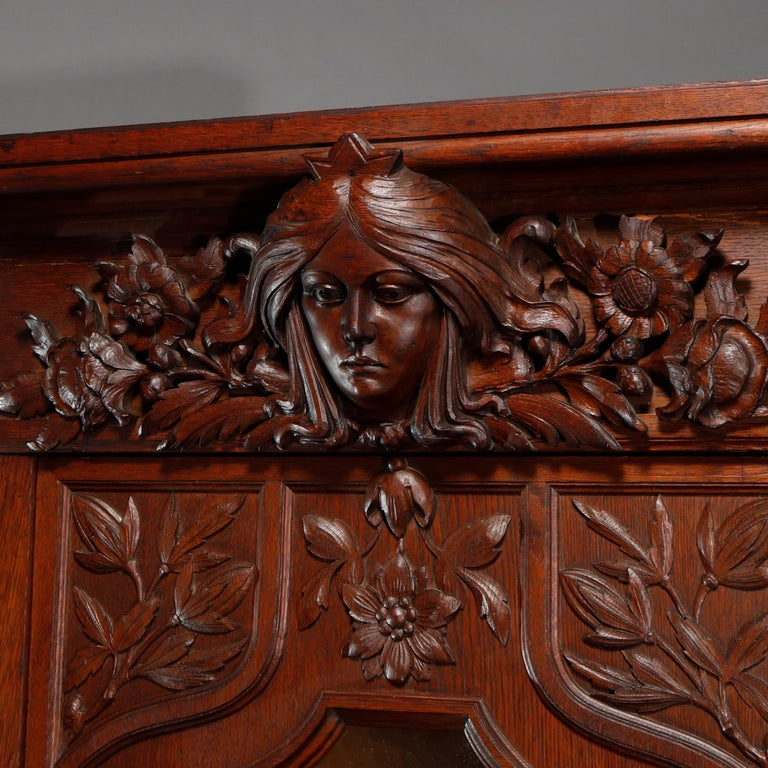 An antique Art Nouveau bookcase offers oak construction with crest having carved Alphonse Mucha style female mask of Sarah Bernhardt with flanking floral elements surmounting case with central cabinet having leaded slag glass door with lily pads