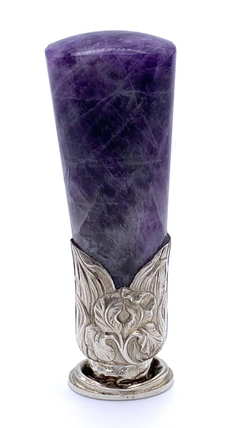 Unusual seal with a chunky violett fluorite handle mounted in silver as an iris flower. The oval seal bears the initials  French makers mark in a lozenge: L (image of a duck ) M