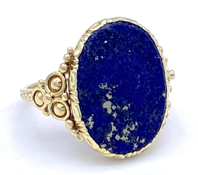 The elegant late Art Nouveau lapis lazuli signet ring is made out of 14 k gold. The oval lapis plaque has natural silver and gold inclusions.  ring size: EU 51 / US 5.25
